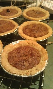 Canadian Butter Tart.    Possibly descended from  Sugar pie (tarte au sucre): maple syrup, butter and dried fruit  Pecan pie  Backwards pie: which is found in the maritimes and western Canada and made with corn syrup,  Shoofly pie: which is made with molasses  Treacle tart: golden syrup or treacle
