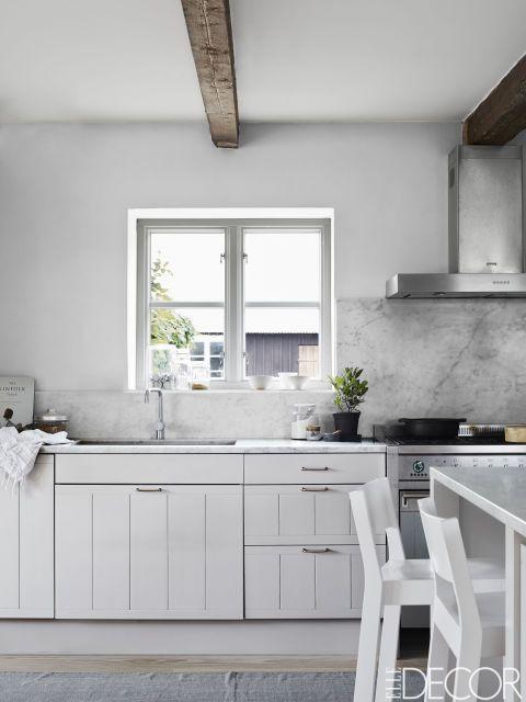 En unacasa rural de Suecia la cocina, la campana extractora y el fregadero son todos de Smeg ylos grifos, de Vola. Las encimeras están hechas en mármol de Carrara y los armarios se han pintado con Cornforth White, de Farrow & Ball.
