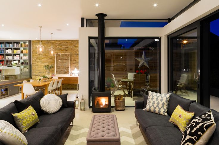 Broadgates Road - Granit Architects. Cosy living area with wood burner, made.com sofas, upholstered ottoman and patterned rug. Pops of colour and pattern in soft furnishing. Rear extension in Wandsworth, South West London.