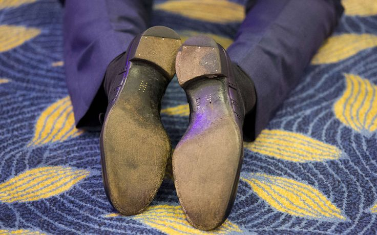 Brass shoe tacks forming the letter 'H'  on the soles of Britain's Prince Harry's shoes as he kneels to speak with award winners whilst attending the WellChild Awards in London