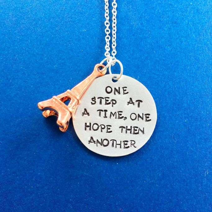 """Journey To The Past Necklace Inspired By Anastasia Broadway Musical This hand stamped pendant reads, """"One step at a time one hope then another""""- a reference to both the classic animated film and upcoming Broadway musical, Anastasia. Alongside the sterling silver filled disc is a tiny rose gold plated Eiffel Tower charm."""