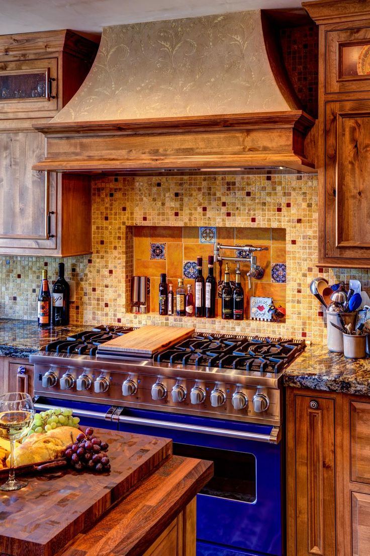 Rustic wood kitchen cabinets with beautiful wood grain are paired with dark brown countertops and earth-toned tiled backsplash in this Mediterranean kitchen. A pro-quality bright blue oven adds a burst of color to the space.