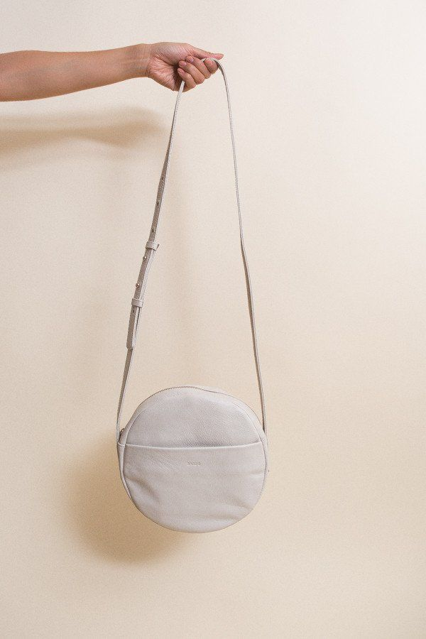 A simple geometric cross body bag in stone color, in the softest leather from Baggu. Adjustable strap for over the shoulder or cross body use. Exterior pocke...