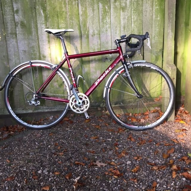 """A medium John Perks custom built A6N aluminium framed winter training bike with carbon forks. The groupset is a mixture of Campag 10 speed Centaur and Veloce with Tekro brakes and Fulcrum Racing 5 wheels. The finishing kit is carbon with a Selle Italia saddle and SPD pedals. The bike would suit a rider of between 5′ 6″ and 5'10"""" tall. The frame and components are all in good condition."""