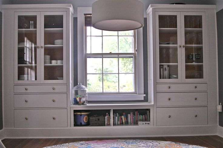 ikea hemnes hack - dining room built ins using hemnes cabinets and extension piece as window seat / bookshelf.  Added mouldings, painted back panel, painted knobs gold.