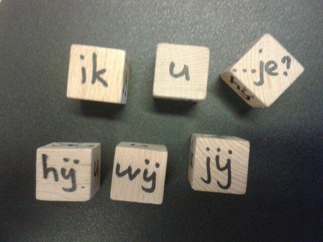 Coöperatieve werkvorm spelling. Nummer 1 noemt een werkwoord. Nummer 2 rolt de dobbelsteen. Nummer 3 zegt de zin en de regel.  Iedereen schrijft en controleert.