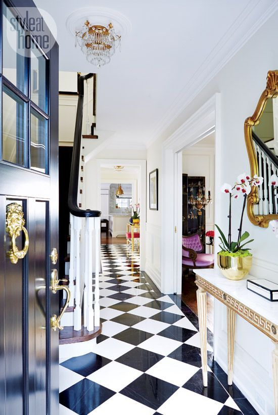 A marble harlequin floor, high-gloss black banister and crystal light fixture set the vintage glam vibe to the rest of this house.