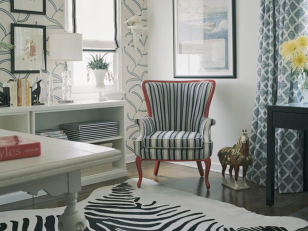 Designer Erinn Valencich uses a white Roman shade outlined in black trim to continue the black-and-white color scheme of the office.