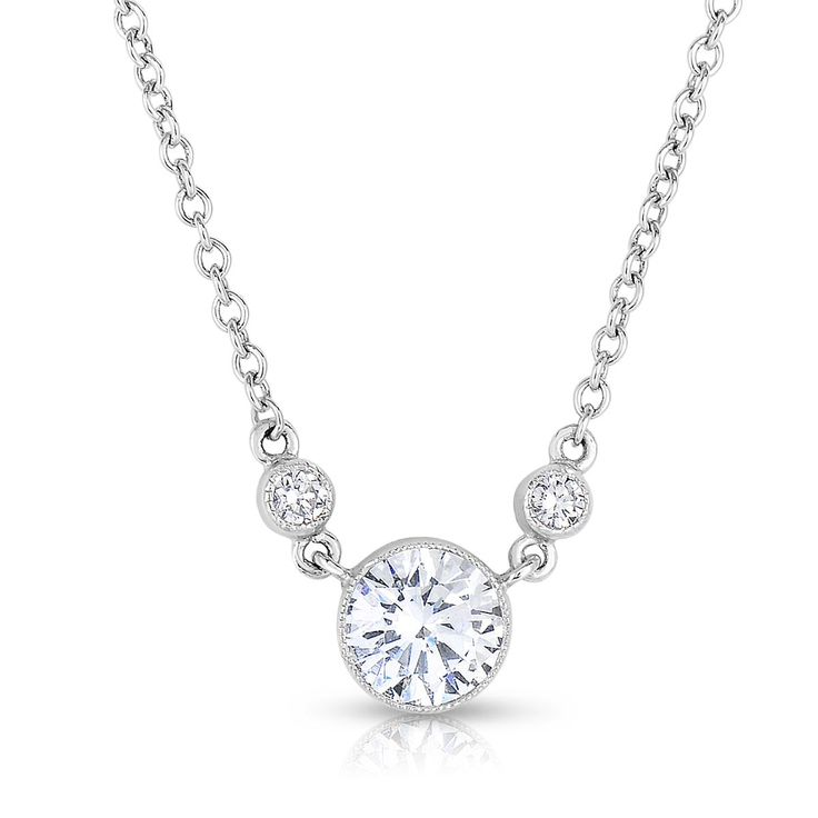 One large round-cut bezel-set diamond is decorated by two chic side stones to create this simple yet suave pendant necklace. Designed with 18k white gold with a high polish finish, this jewelry secure