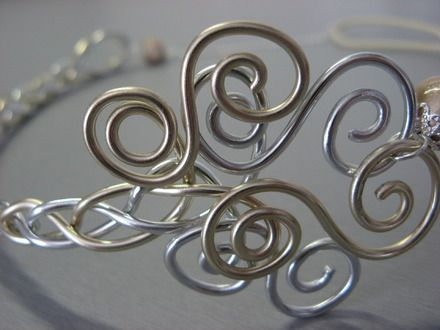 Head band de style légèrement rétro et romantique à souhait; il est composé d'un élégant motif en spirales prolongé par une tresse, en fil aluminium perle et argenté. Le  - 10426553