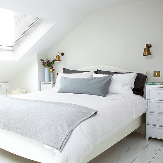 The small eaves-style space of this double bedroom is maximised with plain white walls and painted wood flooring.