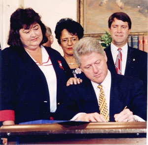 Image of Bill Clinton signing the Ryan White Care Act while White's mother looks on.