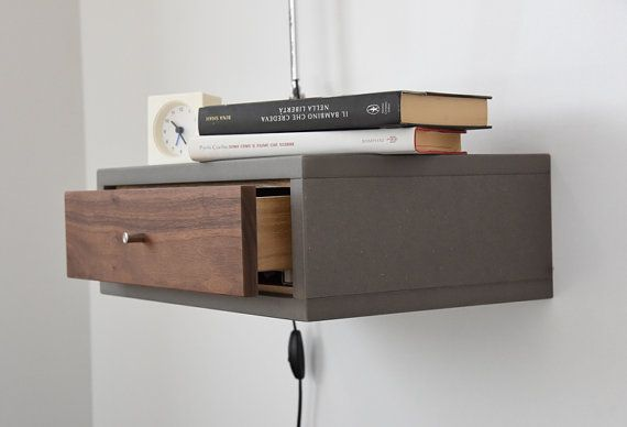 Hermosa mesa/mesita, flotante diseño escandinavo de mediados del siglo. La consola está diseñada para flotar en la pared, adosada a la muralla, maximizando el uso del espacio en dormitorios pequeños. Perfecto para integrar con una lámpara, reloj y reserva en un pequeño espacio. El cajón que puede sacar totalmente gracias a una mecánica de alta calidad guía (BLUM). El frente es de madera de nogal aunque la estructura es en gris VALCROMAT. Nosotros hemos proporcionado esta pieza para que p...