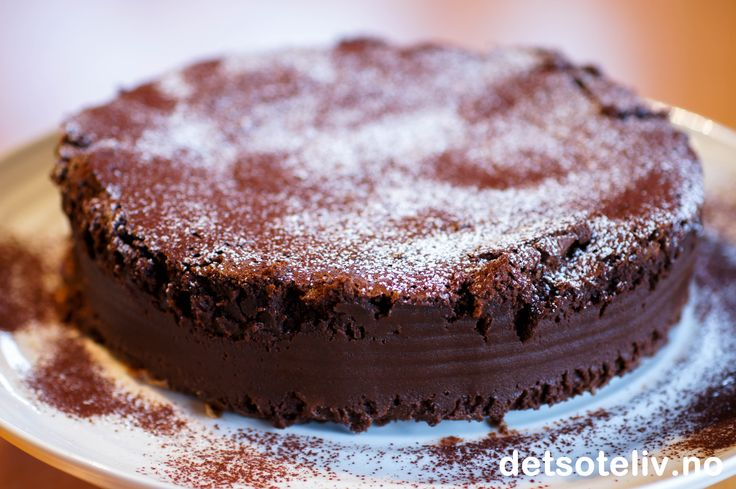 """Maken til sjokoladekake finnes knapt i hele verden! Oppskriften på legendariske """"Chocolate Nemesis"""" stammer fra """"River Café"""" i London - en liten, italiensk restaurant ved Themsen, som omtrent ikke har hatt et eneste ledig bord siden åpningen i 1987 og som i 1998 fikk sin velfortjente Michelin stjerne. Sjokoladekaken inneholder ikke noe hvetemel og kjennetegnes av sjokoladen som smeltes sammen med sukkerlake, og at kaken stekes i vannbad. Konsistensen er kremete og helt, helt unik! Smaken av…"""