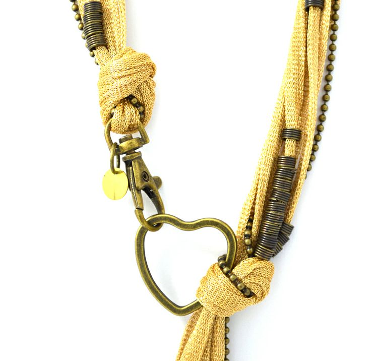Gold metallic cord decorated with brass beads, chain and heart charm.