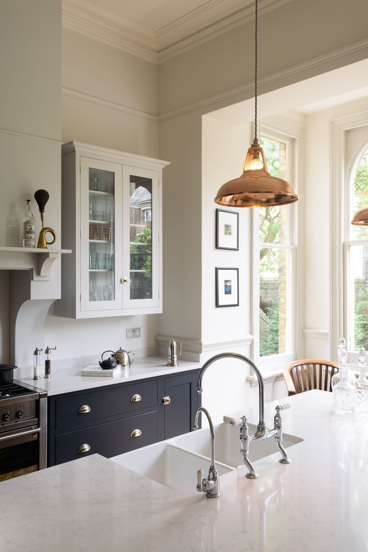 Hardwearing pale Silestone worktops and chrome taps look beautiful in this Shaker Kitchen by deVOL