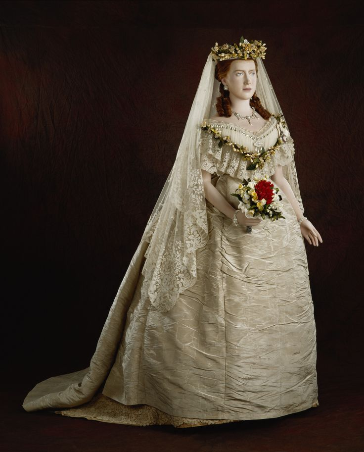 Princess Alexandras wedding dress, comprising: a cream silk bodice with low drawstring neck with Honiton lace and net trim, short puff sleeves with orange blossom sprigs; the skirt with flat front and six panels, gathered into train at the back, with a wide needle-lace trim, all lined with brown silk and stiff muslin.Princess Alexandra was the first member of the Royal Family to be photographed in her wedding dress. 1863