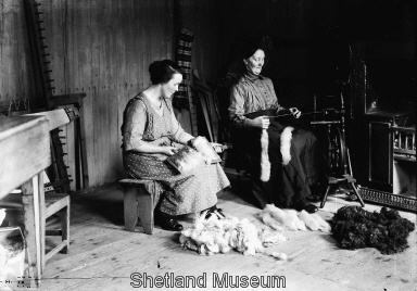Carding Wool and Spinning Wool, notice the pile of rolags at the spinners feet.