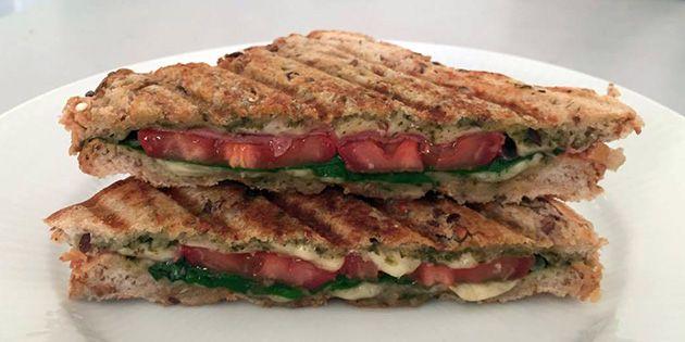 Lækker og sprød hjemmelavet panini med pesto, skinke og masser af smeltet ost. Paninien tager ingen tid at lave, og den smager helt vildt godt.
