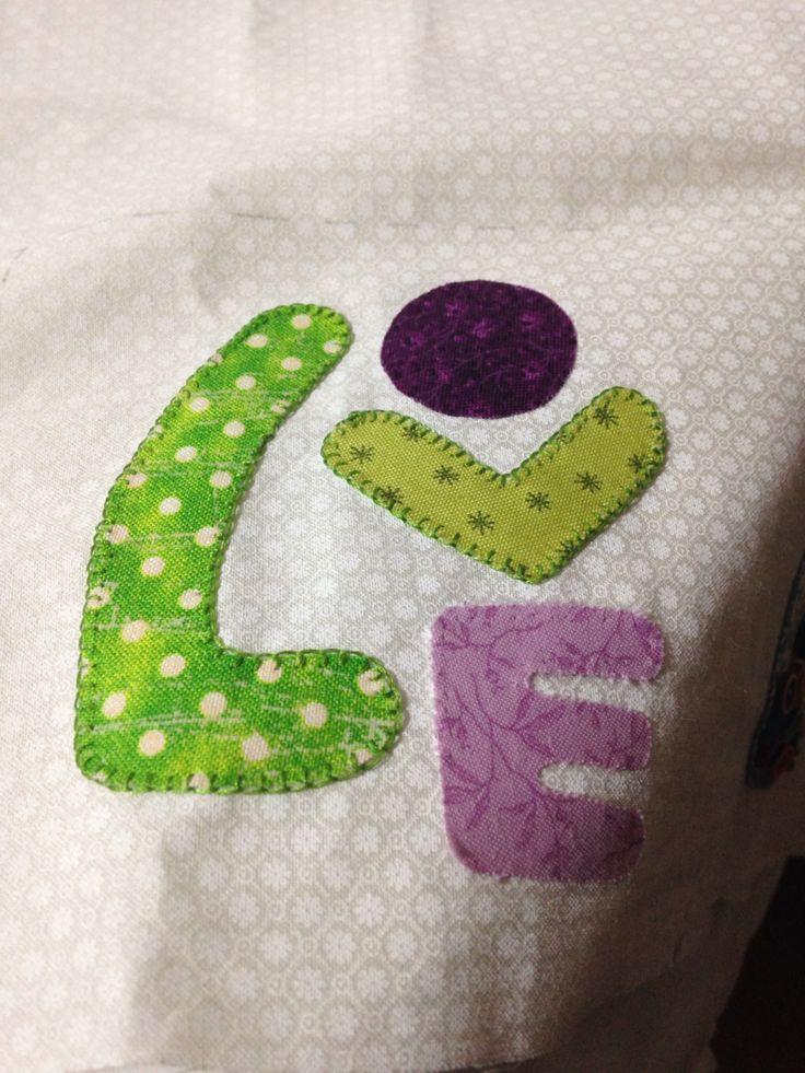 Recortar las letras en cartulina, luego pasarlas a papel pellón, recortar y pegar con plancha caliente sobre el revés de la tela, finalizo con puntada pañal para los bordes, sencillo y bonito