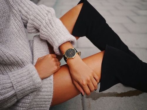 Thick knit sweater dressed up with tall black boots and a simple black watch