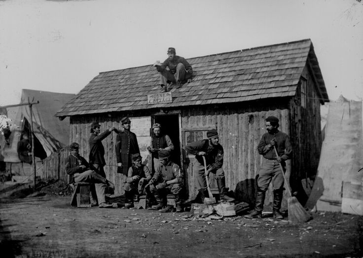"""Civil War: Soldiers in front of their winter quarters - wooden hut, """"Pine Cottage,"""" 1864"""