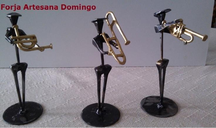 Figuras de músicos elaboradas con clavos de herrar. Trío de metales tocando trompa, trombón y trompeta.