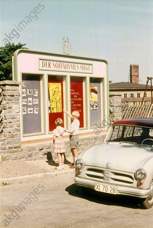 """Kinder vor einer Plakatwand mit politischer Propaganda """"Der Sozialismus siegt"""".   Foto, o. O. u. J., um 1956 (Werner Hoffmann)."""