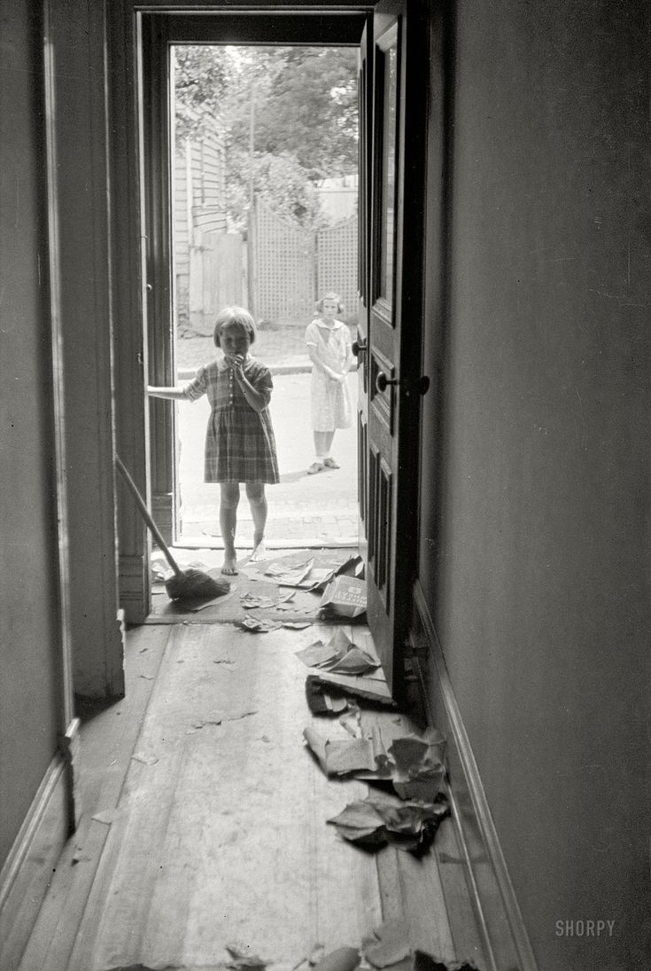 """Poor White Hallway: September 1935. Washington, D.C. """"Poor white hallway, Georgetown. Seldom do these people have even the desire to clear up rubbish, and the broom shown here seems to be out of place."""" 35mm nitrate negative by Carl Mydans."""