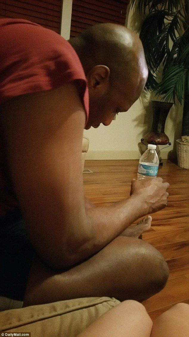 Disheveled: Lamar Odom seen wearing a red t-shirt and shorts and holding a bottle of water in the room where he spent four days after arriving at the brothel on Friday