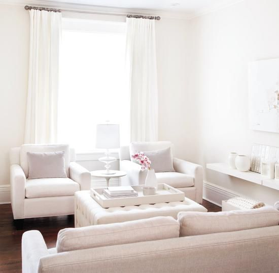 source: Style at Home     Ann Marie Favot - Monochromatic living room design with white linen sofas & chairs, off-white ivory tufted ottoman, white lacquer tray, Saarinen marble tulip accent table, white drapes, lilac pillows, glass lamp and floating shelves.