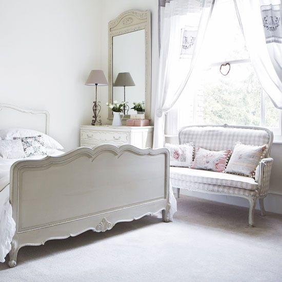En esta habitacion, los paredes son blancos y la alfombra es blanco, tambien.  La cama es blanco con un poco rosado.  Una lampara es encima de una mesa.  La habitacion tiene una ventana grande y un sofa blanca y rosada.