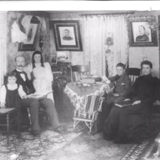 "Thomas A Hillary (2nd left) and his Wife Elizabeth Osborne Hillary (far right) in their living room around 1896, Cornwith, Iowa. Children: CliffordHillary, far left (still in his ""skirts"") Betha Hillary, centre Alfred Hillary, 2nd from right Pictures on the wall (left to right) are belived to be Mary Hillary (died aged 6) Thomas Hillary (1818 - 1860) Faith Hillary, nee Hodsgon (1818 - 1904)"