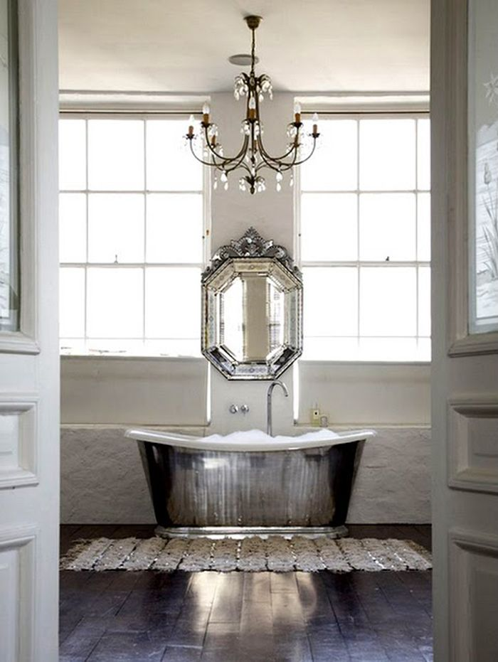 Love the Moroccan wedding quilt used as a rug in front of the bath tub here! #bathroom #sequins