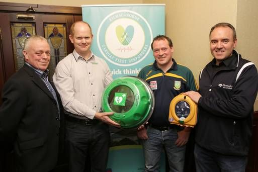 John Hopkins chairman of Kilmac Community First Responders, Ken O'Dwyer from Flashpoint and David Greville from Heart Safety present the new cabinet and defibrillator to Marc Quinn, Ireland