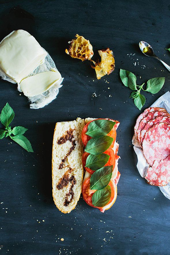 Sandwich roasted garlic, salami, mozzarella, tomato, and basil between a crusty baguette. Image Source: Say...