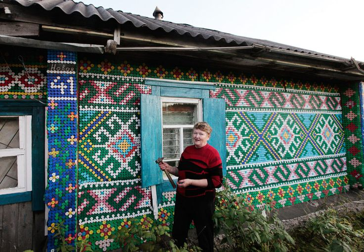 Pensioner Olga Kostina poses near a mosaic, made from plastic bottle caps, which decorates the facade of a courtyard building, in the village of Kamarchaga, in the Siberian Taiga area about 80 km (50 miles) southeast of Krasnoyarsk, Siberia, on September 10, 2012. Kostina used more than 30,000 colored caps to decorate her house and other constructions in the courtyard.