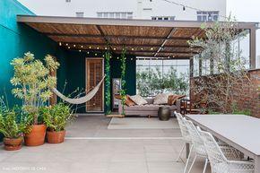 Área externa tem parede de tijolinho, balanço, rede e espaço para refeições ao ar livre.