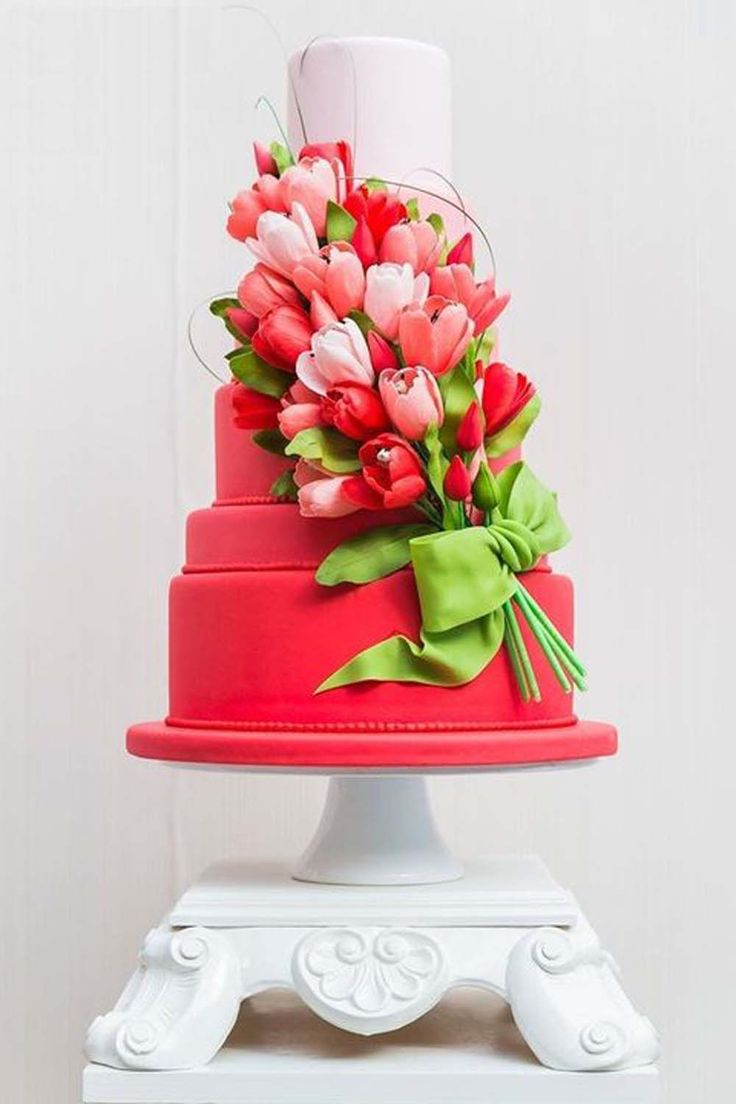 For a spring wedding choose an ombre cake decked with pink and red sugar tulips. The green fondant bow and leaves add a gorgeous contrast.