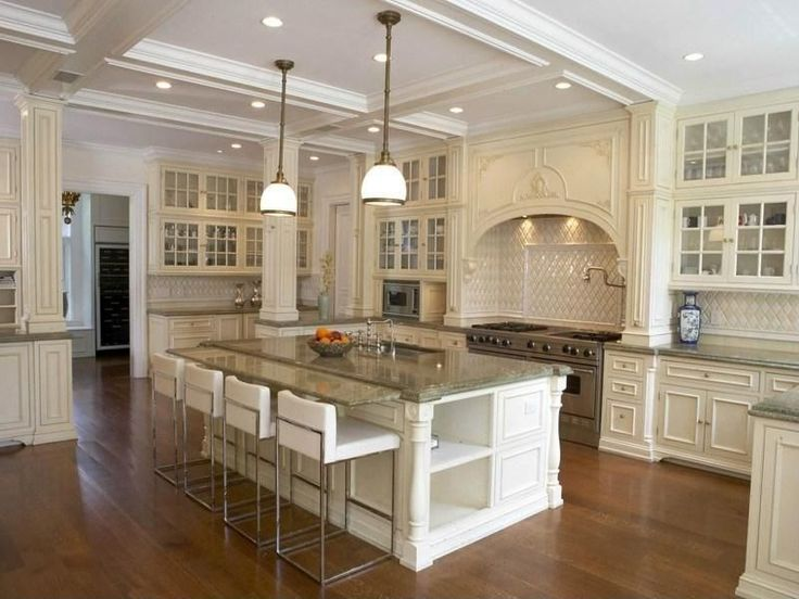Traditionally ornate kitchen with filigreed wood cabinetry, patterned tile backsplash and ceiling detail over large island with marble countertop.