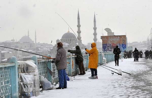 Snow falls as people walk and anglers fish on Galata Bridge in Istanbul, on January 8, 2013.