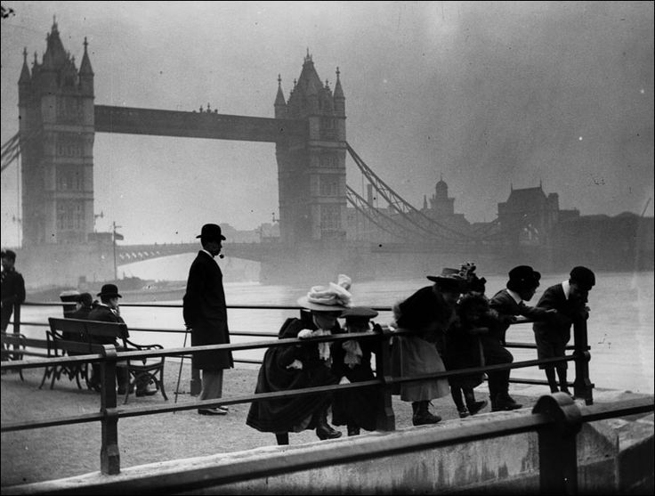 Children peer over the railings by the banks of the river Thames in London with Tower Bridge in the background.    photo by F J Mortimer