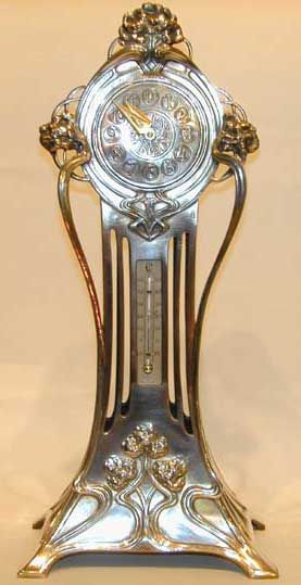 ManufacturerWMF  Designer  DescriptionPolished pewter clock and thermometer with original movement and Art Nouveau floral decoration  Country of ManufactureGermany  Date1906  MarksMarked to base  ConditionPerfect  Size  Other Information