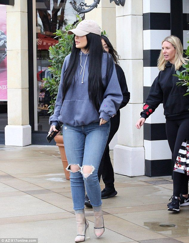 Laid-back: She teamed her designer curve-enhancing pants with a casual faded blue Champion...