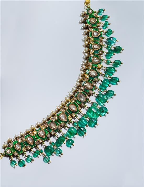 A Yellow Gold, Emerald, Diamond, Pearl and Polychrome Enamel Collar Necklace, Deccan, containing 67 pear shape lasque and rose cut diamonds, 26 cultured pearls measuring 5.63-5.69 mm in diameter, ten square and rectangular cut emeralds and 27 emerald beads measuring from approximately 7.20 x 5.80 mm up to 17.64 x 11.64 mm, the reverse accented in a foliate pattern of red, green and white enamel, joined with a high karat gold link hook-and-eye clasp. 105.50 dwts.