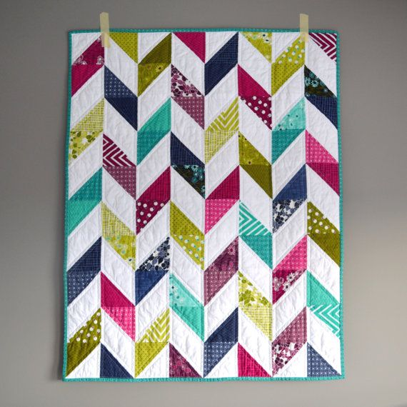 This modern baby quilt is very bright and vibrant making it a great addition to any little girls room/nursery. All fabrics are from the Simply Colorful II collection by V&Co for Moda, which includes a variety of geometric and floral prints, in purple, pink, blue, green, and turquoise.  The quilt is 100% handmade by me and has been machine pieced, quilted, and bound for increased durability so it can be loved by your little one for many years to come. It is quilted using straight lines to…