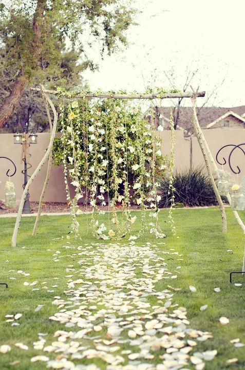 I also like this arch idea as its very pretty but I would probably do the white cloth along the ground with the babys breath pom poms along the aisle