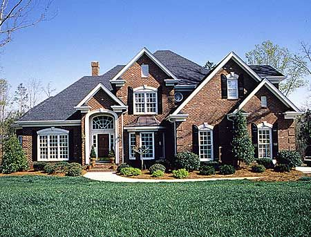 <ul><li>Hipped roof lines, gables, arched windows and shutters set off the charming exterior of this transitional home with a split bedroom design. </li><li>The covered entryway opens to the foyer, from which you see the dining room, demarcated by three interior columns, and the gathering room straight ahead, where the ceiling slopes to 12 feet, 6 inches. Ceilings in the dining room, with an arched window, and foyer also reach this height. </li><li>A fireplace flanked by built-ins anchors…