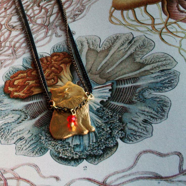 Collar Gato. Gato de latón en acabado brillante, del cuello le cuelga un cristal facetado en color rojo. Doble cadena en acabado pavón y bronce antiguo. Disponible en www.conspiradoras.bigcartel.com