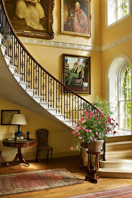 The hall of Bowood House, with its cantilevered staircase, was converted from a dining room in the Fifties, under the direction of John Fowler. The soft yellow walls are a perfect compliment to the wooden floors.